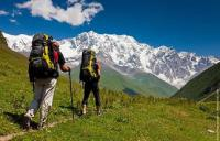 двое туристов идут по маршруту в горах