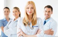 четверо врачей стоят и улыбаются